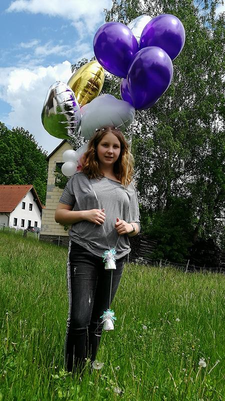 Deklica Melanie, uporabnica PV, z baloni na vrtu