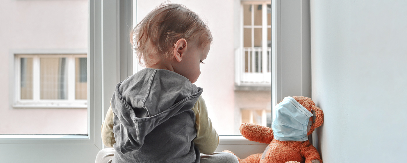 A baby looks at a teddy with a face mask